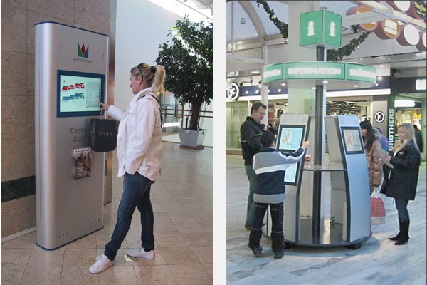 Touch screen information columns in use at shopping centres.